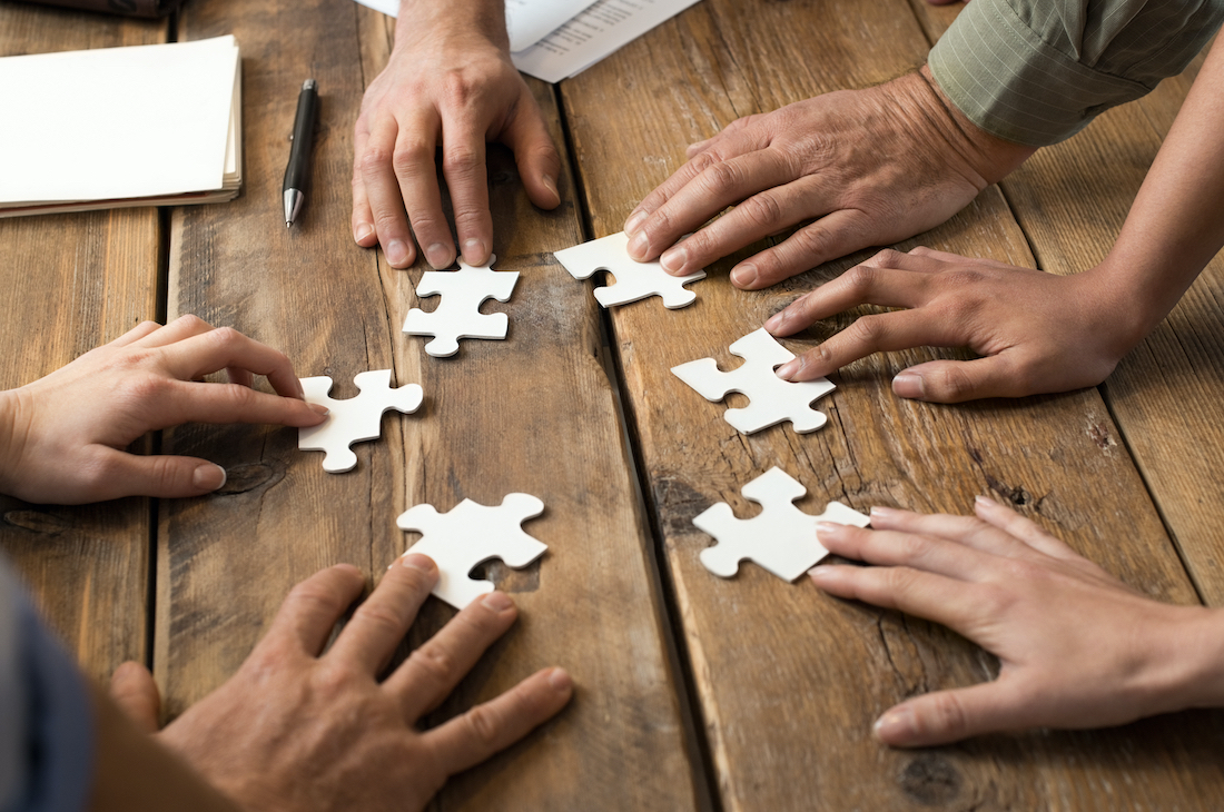 Hands of different people each holding a jigsaw piece