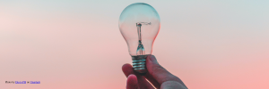 Lightbulb being held in front of a red sky